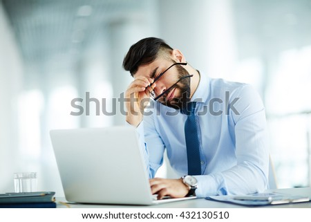 Businessman at his workplace tired of work - stock photo