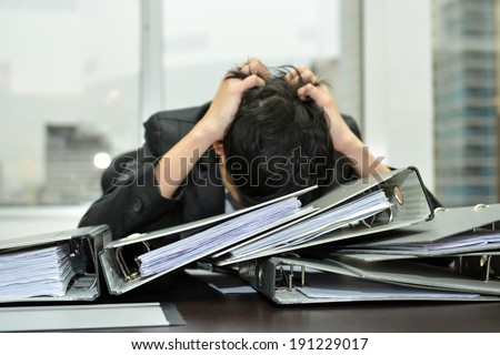 businessman at office desk overloaded with work.