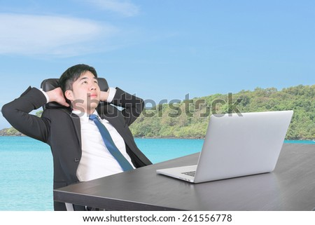 Businessman at office thinking and dreaming about summer vacation travel go to the sea in next holiday - stock photo