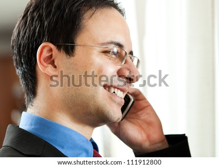 Businessman at phone in his office near the window