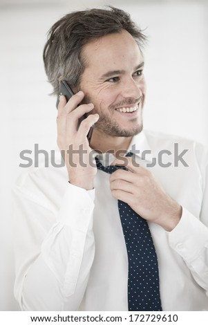 businessman at phone take off his tie - stock photo