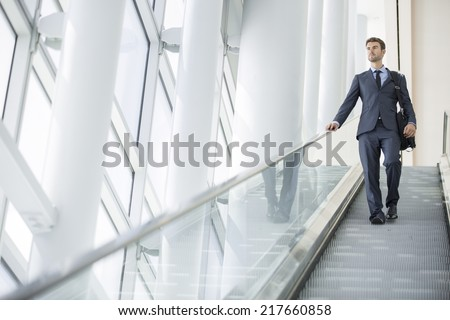 Businessman at the airport going down the escalator - stock photo
