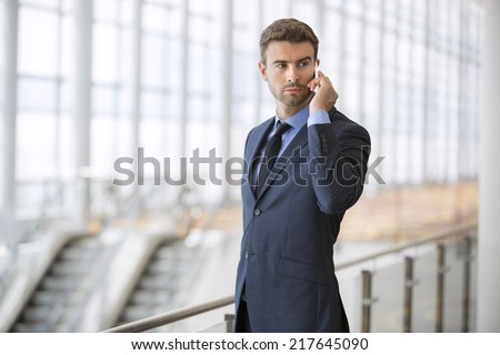 businessman at the airport with mobile phone - stock photo