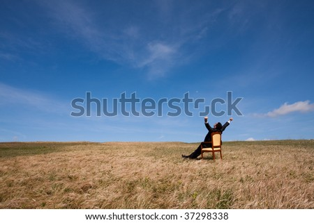 businessman at the field relaxing and enjoying nature