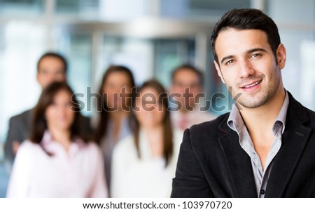 Businessman at the office with a group at the background - stock photo