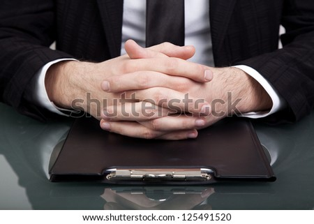 Businessman at the office with his hands folded - stock photo