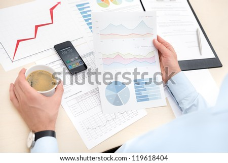Businessman at the workplace drink coffee and looking some business papers with charts, graphs and numbers.