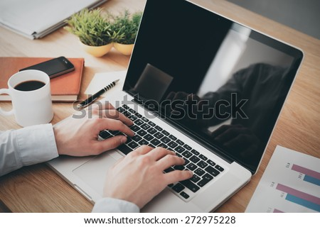 Businessman at work. Close-up top view of man working on laptop while sitting at the wooden desk  - stock photo