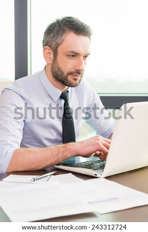 Businessman at work. Confident mature man in shirt and tie working at laptop while sitting at his working place
