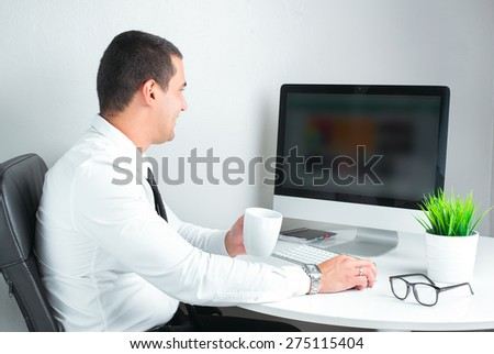businessman at work , drinking coffee and using computer - stock photo