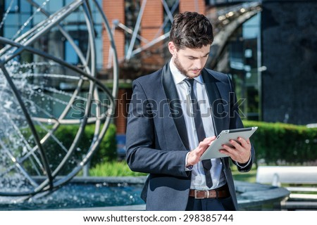 Businessman at work outside the office. Confident and successful businessman holding a tablet and stands near the business center - stock photo