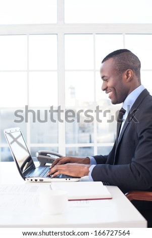 Businessman at work. Side view of cheerful young African businessman using computer and smiling while sitting at his working place