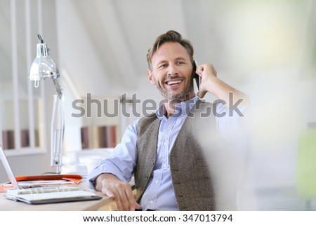 Businessman at work talking on the phone - stock photo