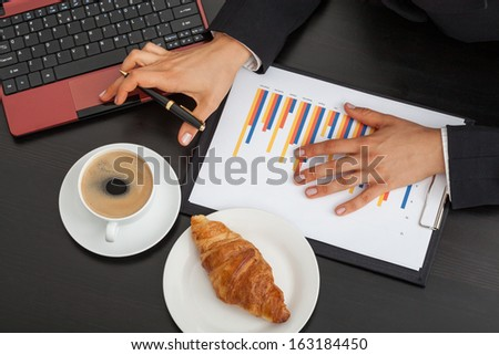 Businessman at work with cup of coffee and croissant