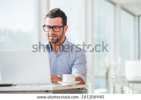 Businessman at work with laptop in his office - stock photo