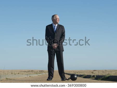 Businessman Attached To Ball And Chain - stock photo