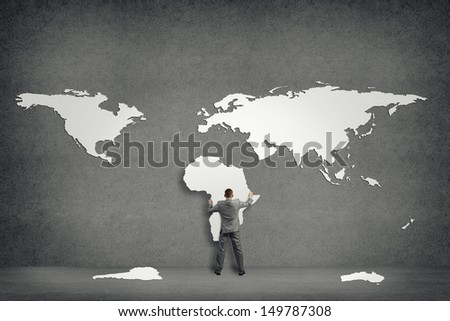 businessman attaches to the wall of the continents, holds the continent of Africa - stock photo