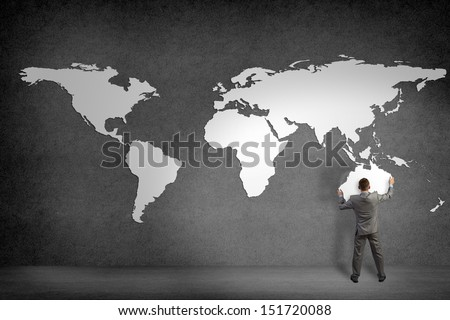 businessman attaches to the wall of the continents, holds the continent of Australia - stock photo