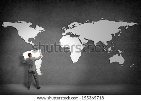 businessman attaches to the wall of the continents, holds the continent of South America - stock photo
