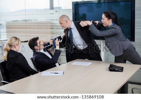 Businessman attacking his colleague at a meeting, grabbing him by the tie and getting ready to punch him in the face. Emotions running high. - stock photo