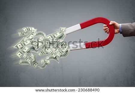 Businessman attracting money with a horseshoe magnet concept for business success, strategy or greed - stock photo