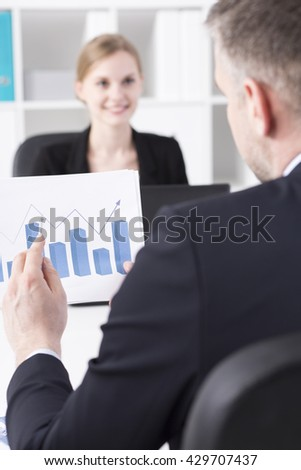 Businessman back biew holding chart, smiling businesswoman sitting in front of him