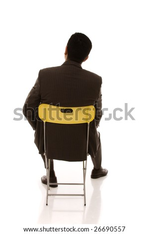 businessman back seated on a yellow chair looking to the copy space - stock photo