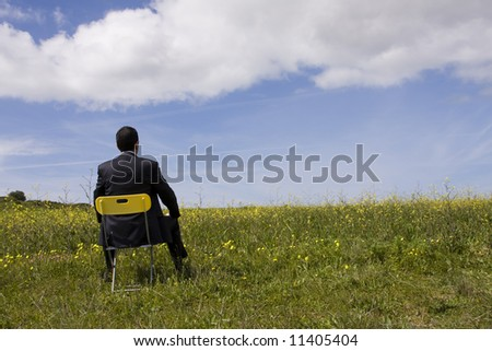 Businessman back sitting in a yellow chair