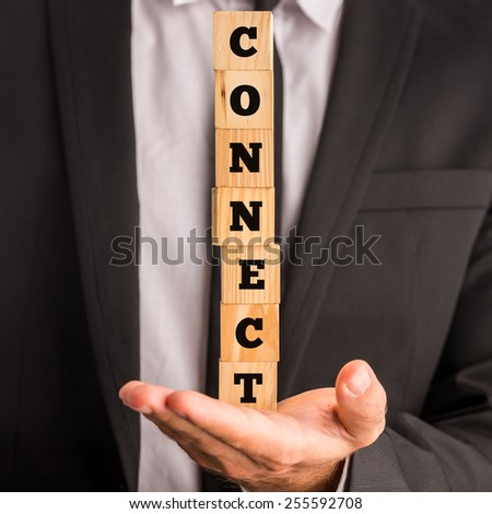 Businessman balancing a stack of seven wooden cubes with the letters CONNECT stacked on his palm. - stock photo