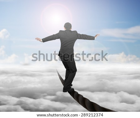 Businessman balancing on a wire with sky sub cloudscape background. - stock photo