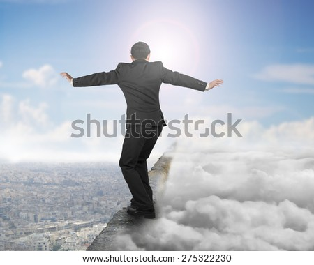 Businessman balancing on old iron chain with sky sunlight cloudscape cityscape background - stock photo