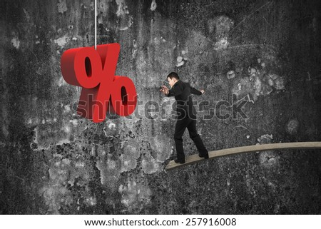 Businessman balancing on wooden board with red percentage sign and mottled concrete wall background - stock photo