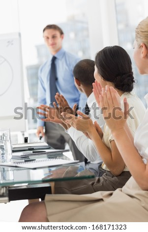Businessman being applauded by colleagues for his presentation in the office