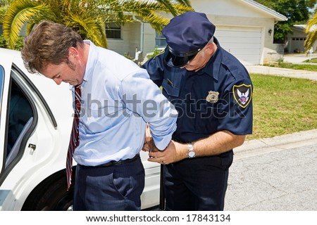 Businessman being handcuffed and placed under arrest in front of his home. - stock photo