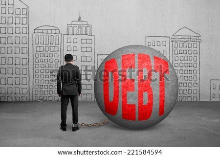businessman being trapped with debt ball and doodles wall - stock photo