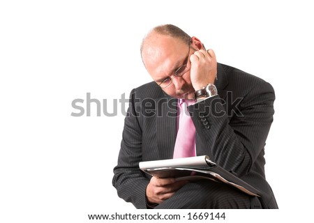 Businessman bend over his notes with a very puzzled and worried look