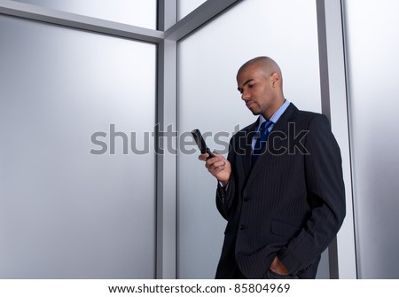 Businessman beside an office window, sending a message with his cell phone. - stock photo