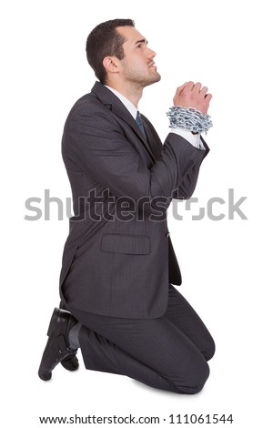 Businessman bound in chains begs for freedom. Isolated on white - stock photo