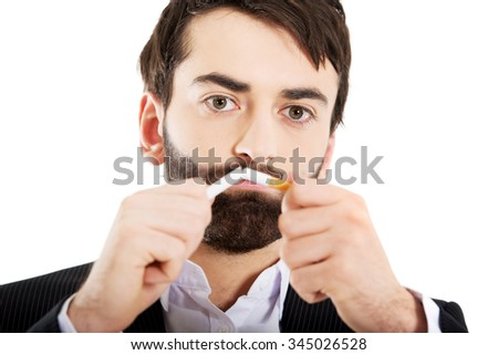 Businessman breaking a cigarette. Stop smoking concept. - stock photo