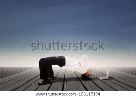 Businessman bridge position over blue sky background - stock photo