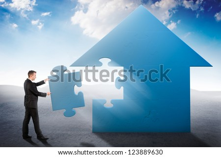 Businessman building a house jigsaw puzzle - stock photo