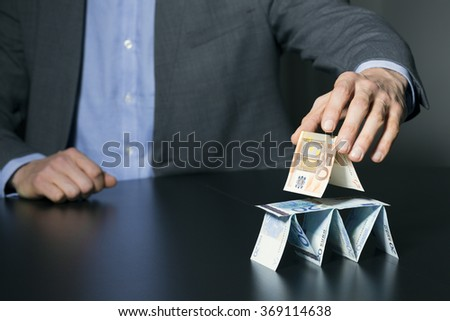 businessman building financial pyramid from euro money - stock photo