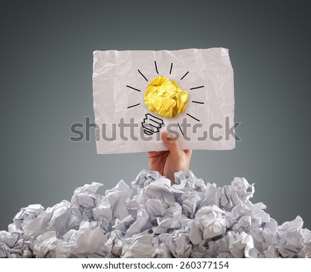 Businessman buried under crumpled pile of papers with an idea sign - stock photo