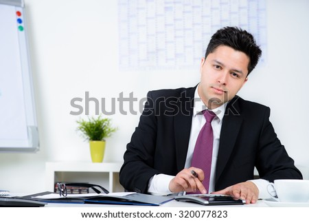 Businessman Calculating Financial Data At Desk