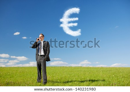 Businessman calling through his cellular phone with Euro Sign from the Clouds