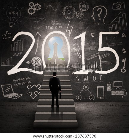 Businessman carrying a briefcase standing on stairway and look at a future doorway of 2015 - stock photo