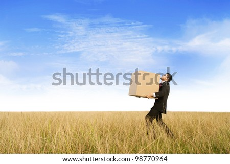 Businessman carrying a cardboard through a marsh - stock photo