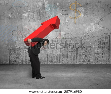 Businessman carrying big 3D red arrow sign with business concept doodles wall - stock photo