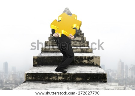 Businessman carrying big gold jigsaw puzzle piece and climbing on old dirty concrete stairs with urban scene background - stock photo