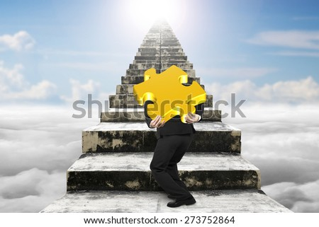 Businessman carrying big gold jigsaw puzzle piece and climbing on old dirty concrete stairs with sky cloudscape sunlight background - stock photo